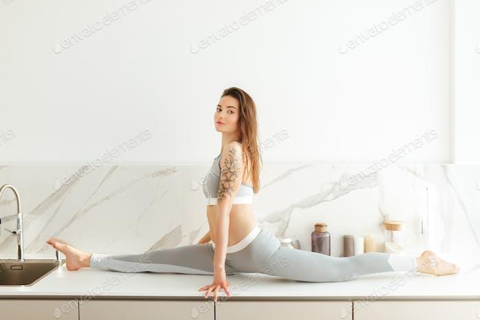 Schöne Dame in sportlicher Kleidung träumig suchen in Kamera Üben Fitness auf Küchentheke