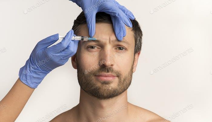 Mature Guy Receiving Anti-Aging Injection Standing, Studio Shot