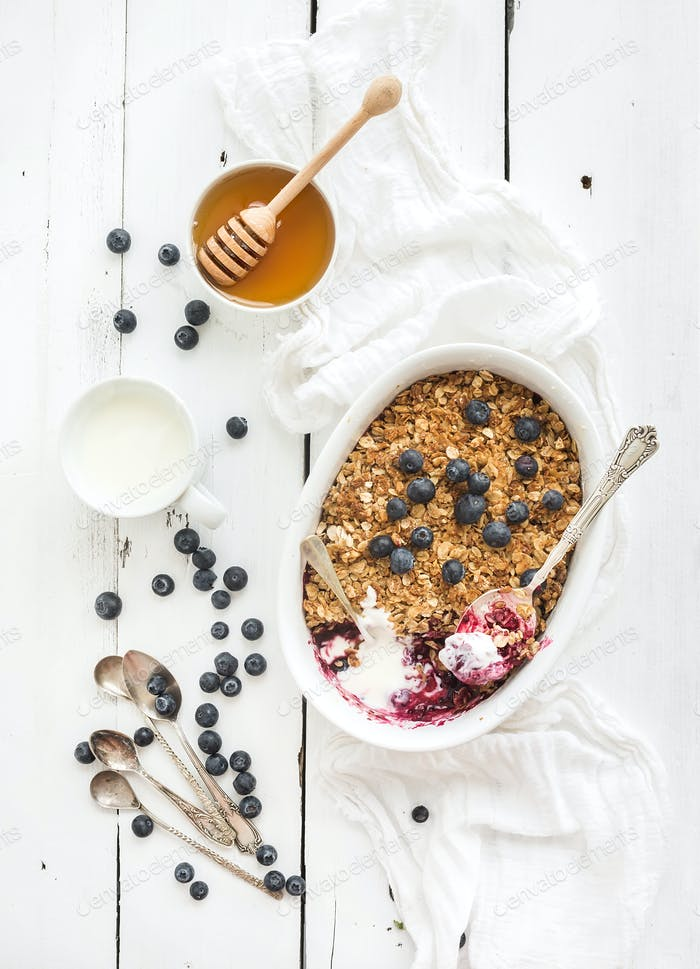 Healthy breakfast. Oat granola berry crumble with fresh blueberries, yogurt and honey