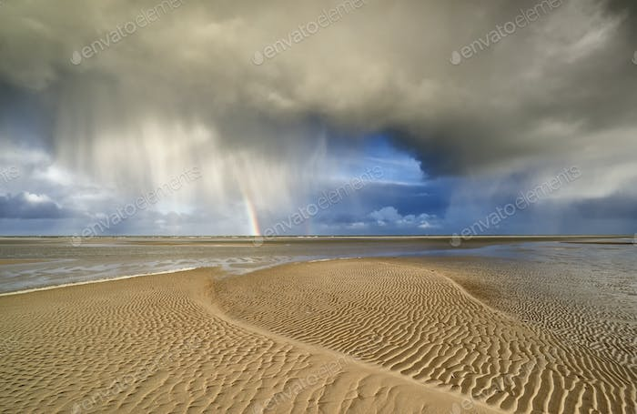 storm cloud and rainbow on sand beach