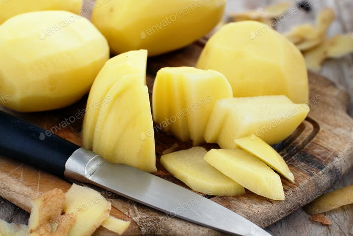 Raw peeled potatoes with a knife