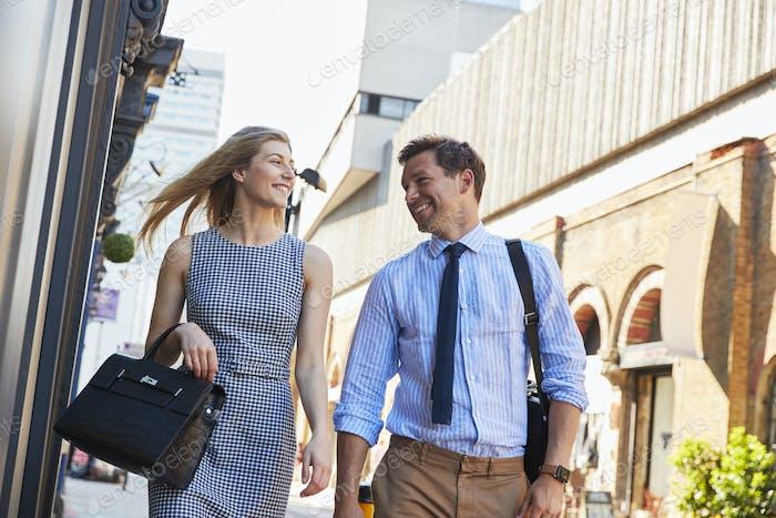 Businessman And Businesswoman Walk to Work Through City Street