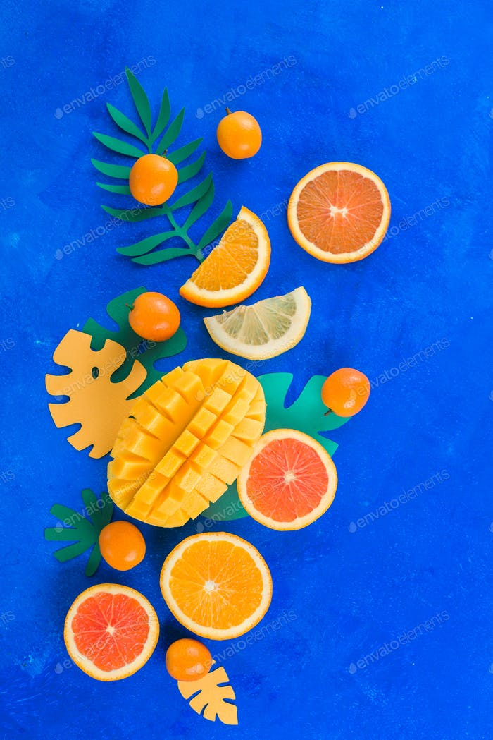 Citrus fruits, mango, oranges, kumquat, and other tropical fruits vibrant blue background with copy