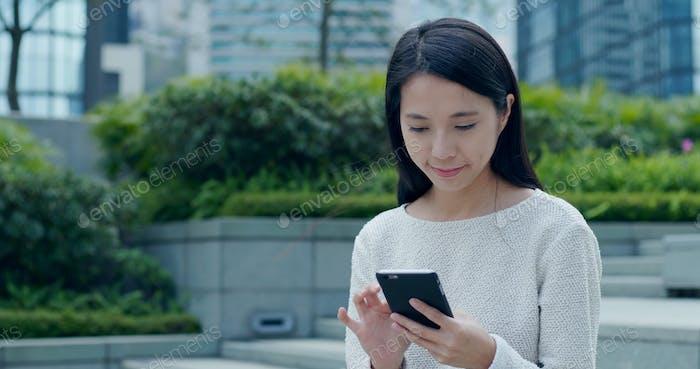 Frau schickt SMS auf Smartphone im Freien