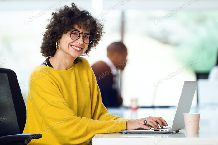 Beautiful hipster businesswoman working with laptop while lookin