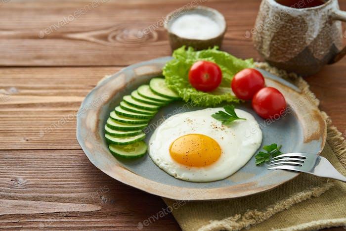 Fried egg, vegetables. Paleo, keto, fodmap diet. Side view. Healthy diet concept, blue plate