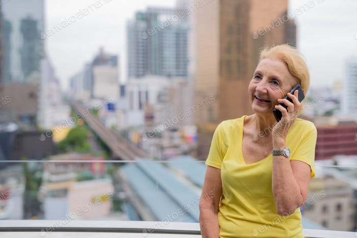 Beautiful senior woman taking on mobile phone in city