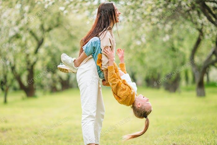 Familie von Mutter und Tochter im blühenden Kirschgarten