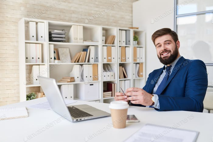 Smiling Businessman Posing at Desk in Office