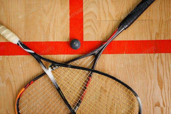 Squashschläger und Ball auf dem Hofboden, Draufsicht