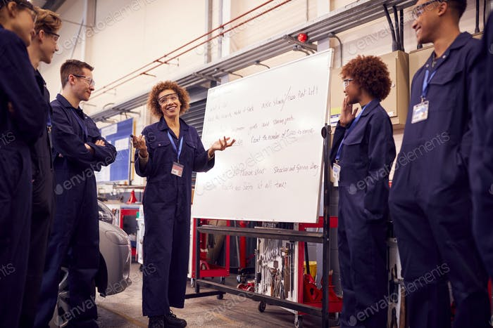 Female Tutor By Whiteboard With Students Teaching Auto Mechanic Leapprenticeship At College