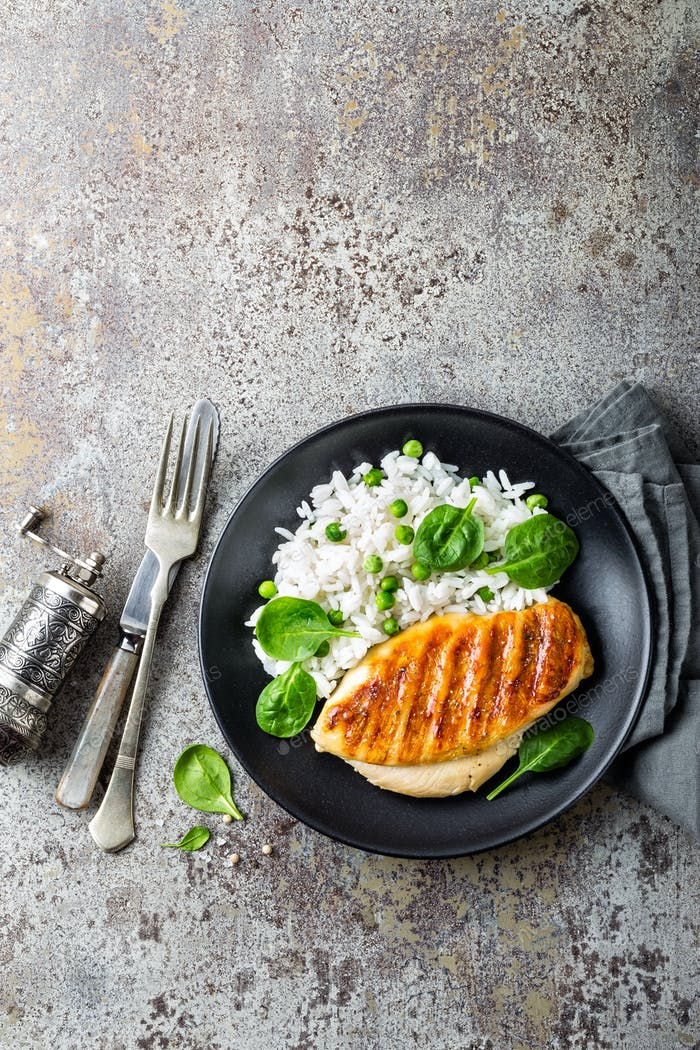 Chicken breast or fillet, poultry meat grilled and boiled white rice with green peas