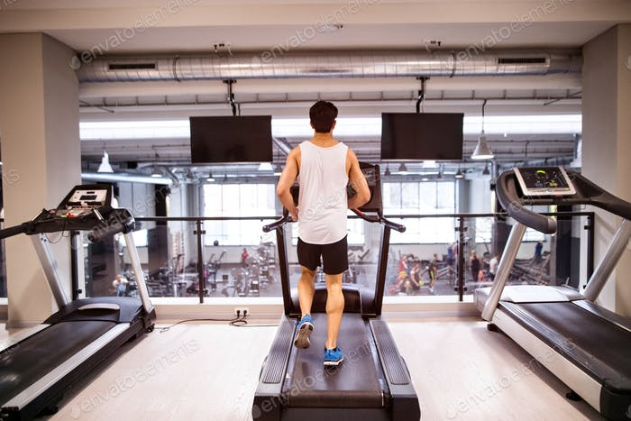 Young fit hispanic man in gym running on treadmill.