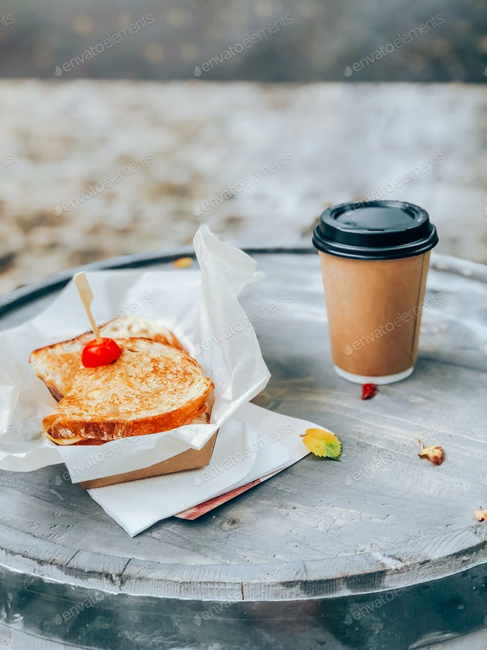 Placeit. Sandwich on paper with coffee. Street food concept