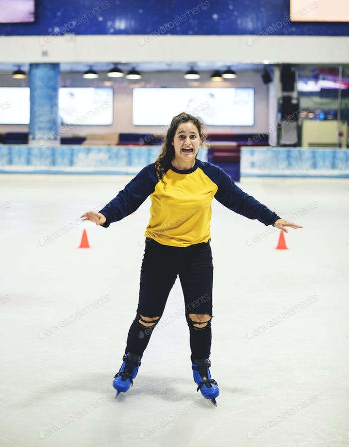 Happy girl ice skating on the rink by herself