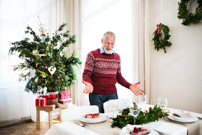 A senior man standing by a table set for a dinner at home at Christmas time.