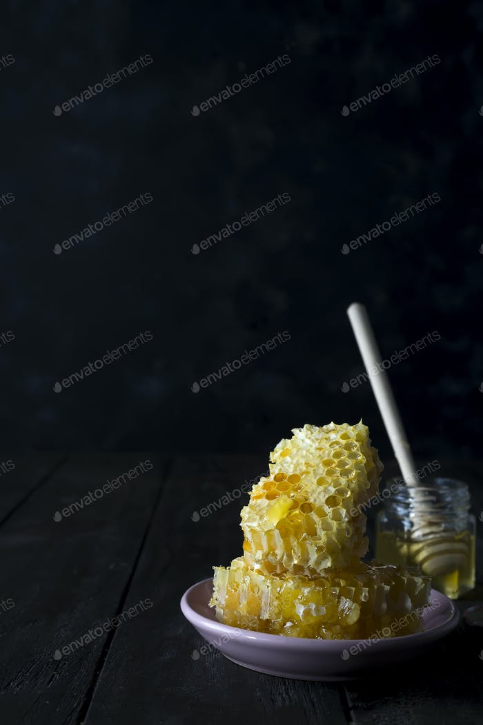pieces of fresh honeycomb with a wooden dipper dripping honey on a ceramic plate