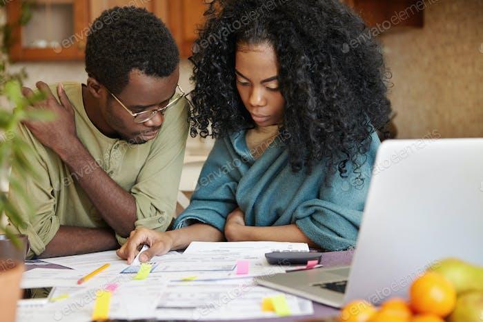 Afrikanisches Paar überprüft seine Finanzen, analysiert das Familienbudget und überlegt, wie die Ausgaben gesenkt werden können
