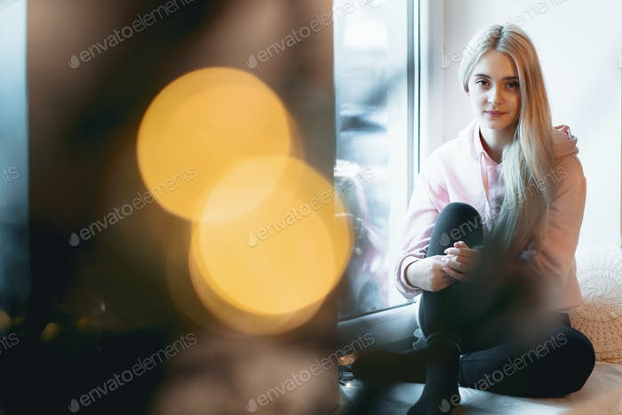 Pretty girl sitting crossed legs by the window with lights refle