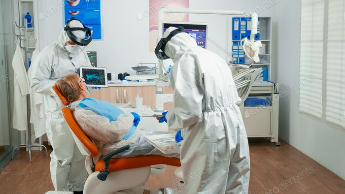 Dentist in protective equipment reviewing x-ray using tablet
