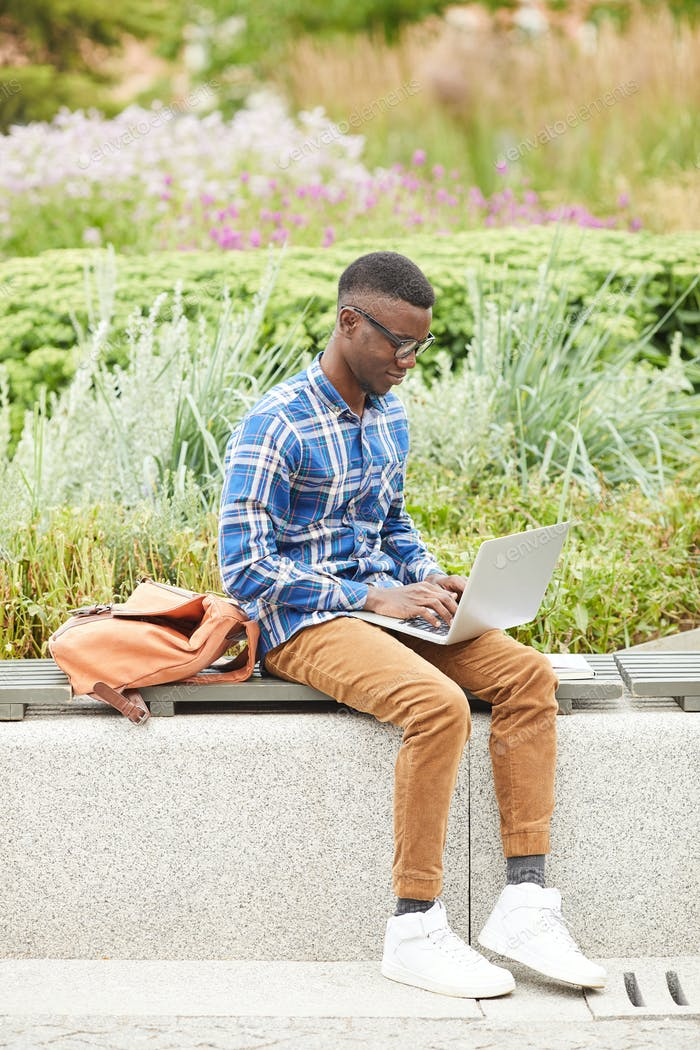 Young African-American Man Using Laptop Outdoors