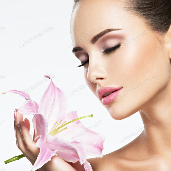 Beautiful woman smells flower. skin care beauty