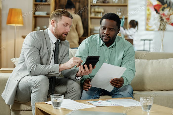Man with adviser calculating mortgage rate