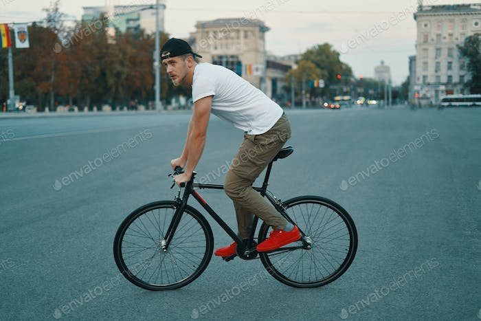 Thumbnail for Young modern man cycling on a classic bike on the city road
