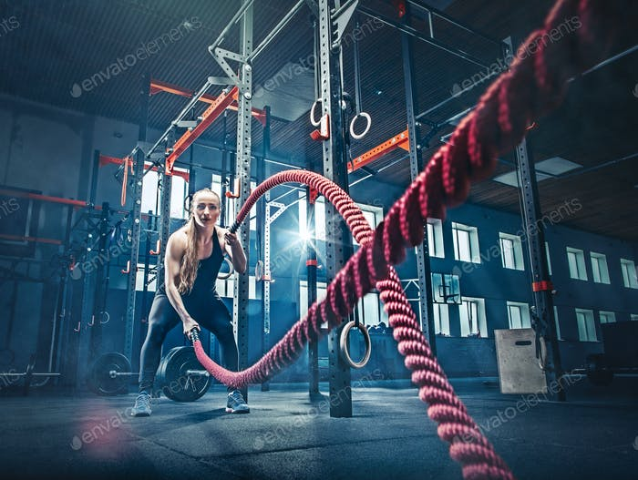 Woman with battle rope battle ropes exercise in the fitness gym.
