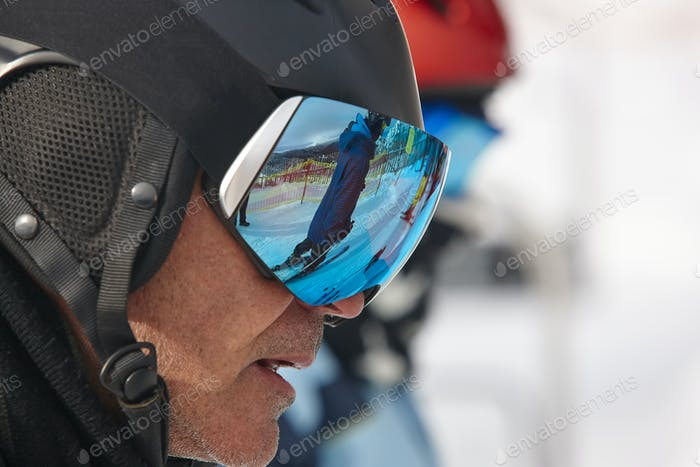 Ski goggles on a white winter landscape. Blue reflection. Horizontal