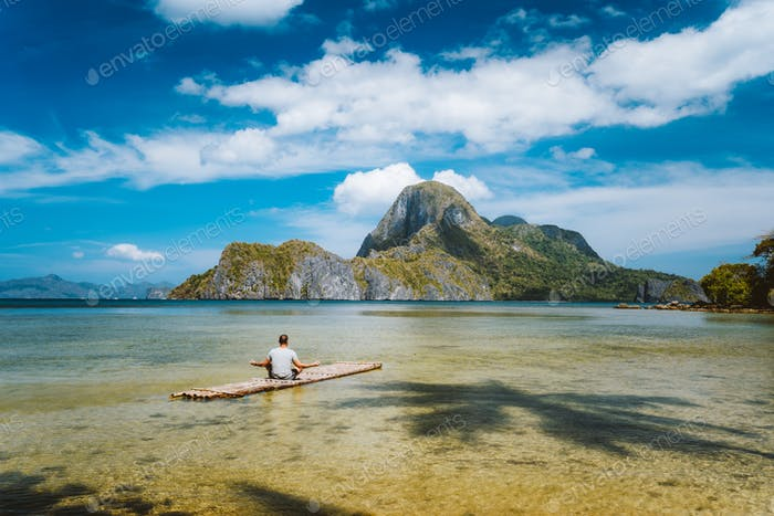 Man meditating on bamboo float surrounded by shallow lagoon water and and Islands of Cadlao bay in a