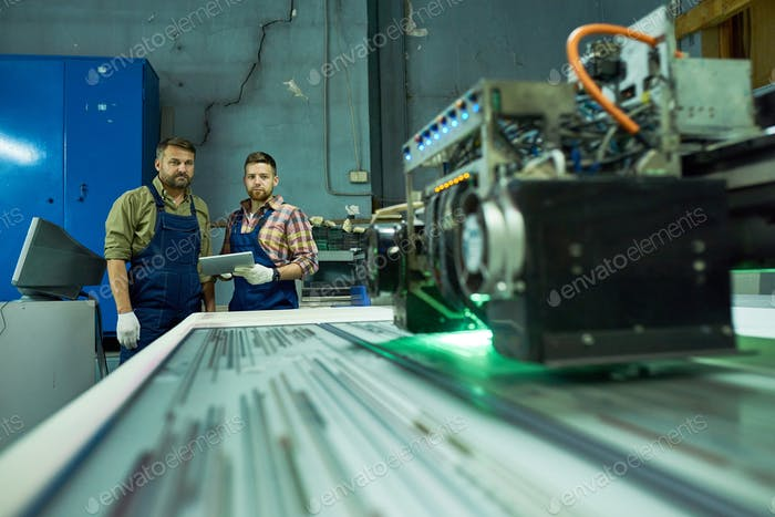 Workers Using Modern CNC Machine at Factory