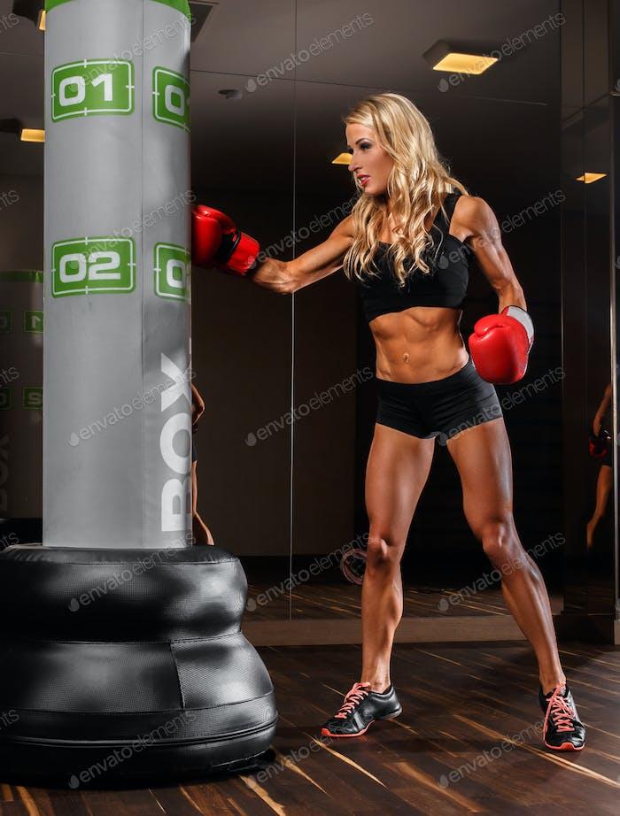 Eine blonde Frau, die in einem Fitnessstudio boxt.