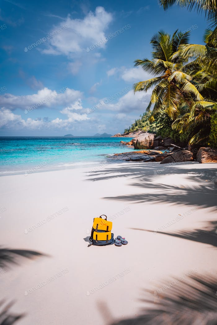 Yellow backpack and flip flops on beautiful tropical sandy beach. Palm trees and blue sky. Holiday