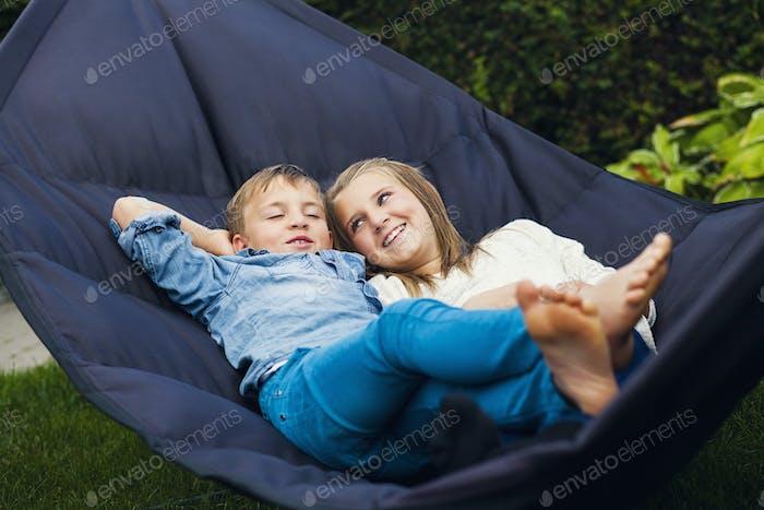 Happy siblings lying on hammock in back yard