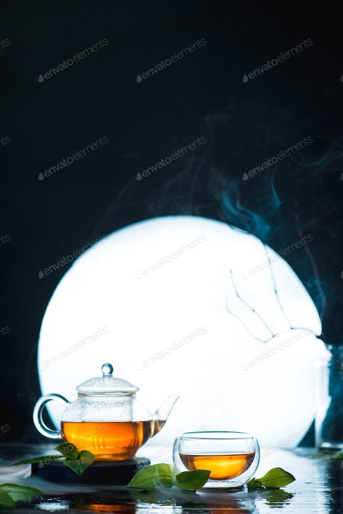 Asian tea ceremony with a full moon. Glass tea bowl and teapot against a shining circle. High