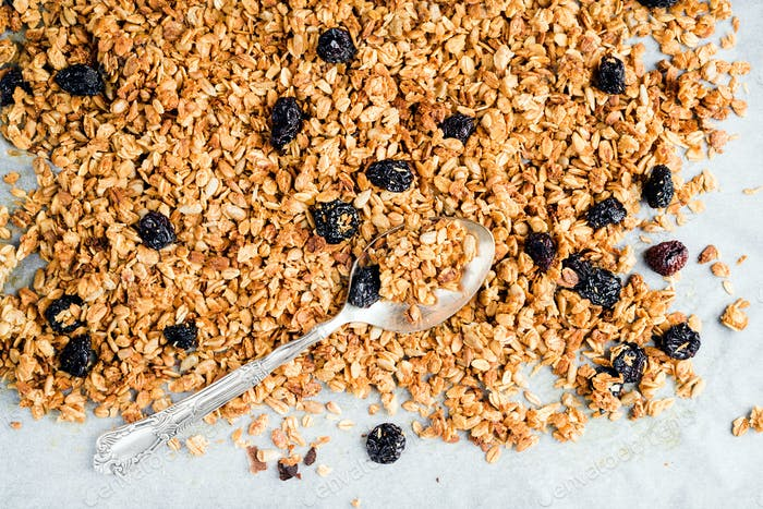 Homemade oat, cherry and coconut granola over baking paper with spoon,