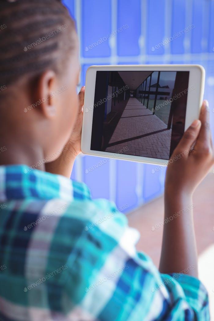 Schoolboy photographing corridor through digital tablet