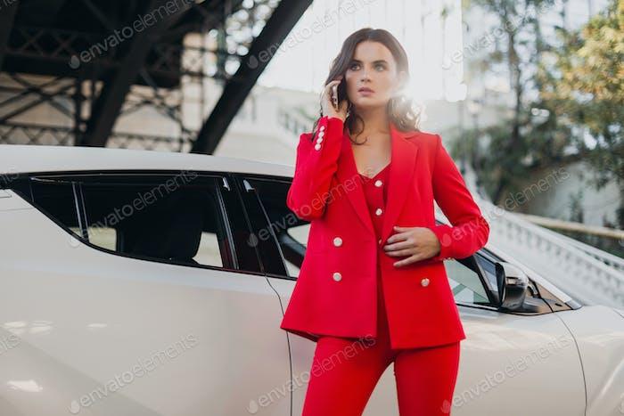 Schöne sexy Frau im roten Anzug posiert im Auto und telefoniert geschäftlich