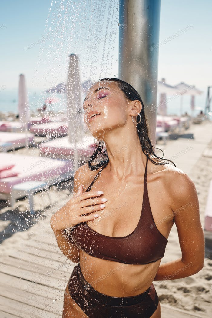 Beautiful sexy brunette girl in wet swimsuit dreamily taking beach shower on a hot day