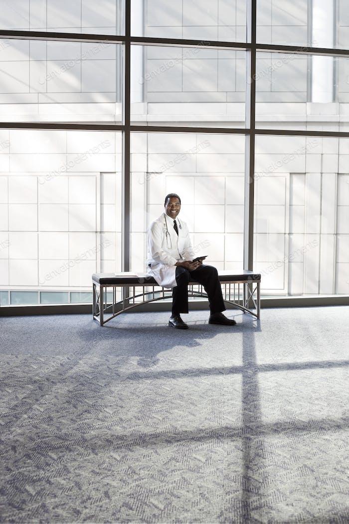 Schwarzer Arzt im Labormantel mit Stetheskop.