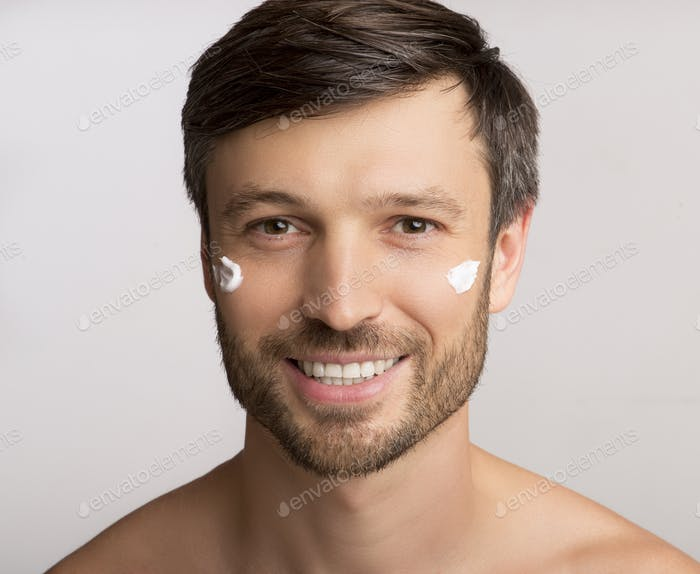 Man Applying Anti-Aging Cream On Face Over White Background