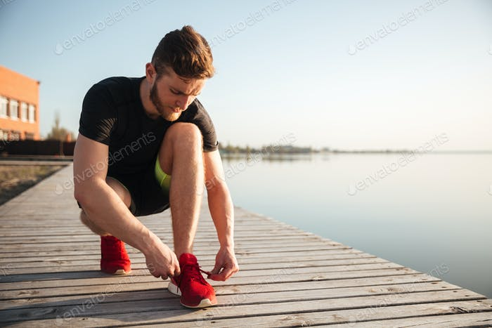 Portrait of a man tying shoelaces on sports shoe