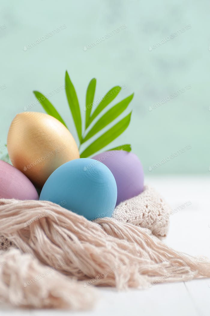 Easter eggs pastel and golden colors on a white wooden table.