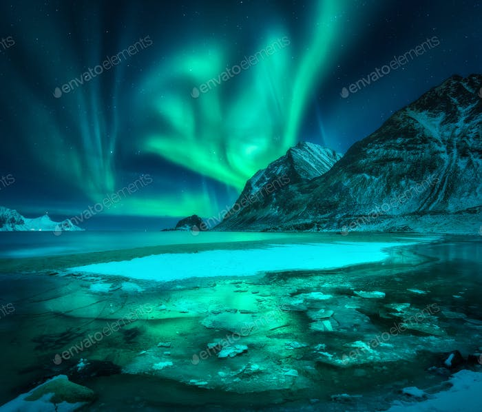Aurora borealis over snowy mountains, frozen sea coast