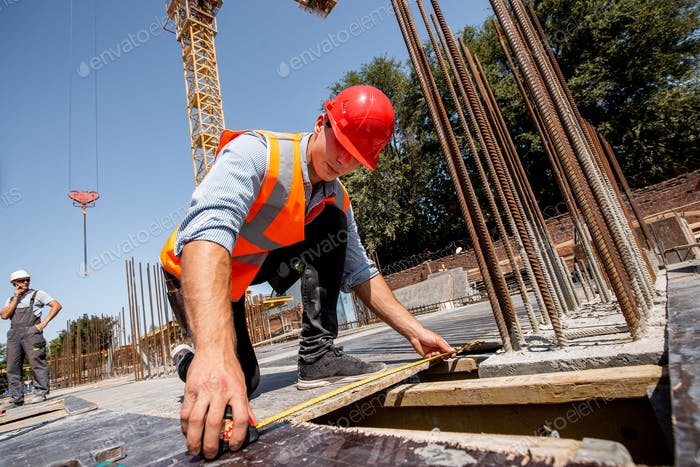 Man dressed in shirt, orange work vest and helmet measures the hole with a tape measure on the