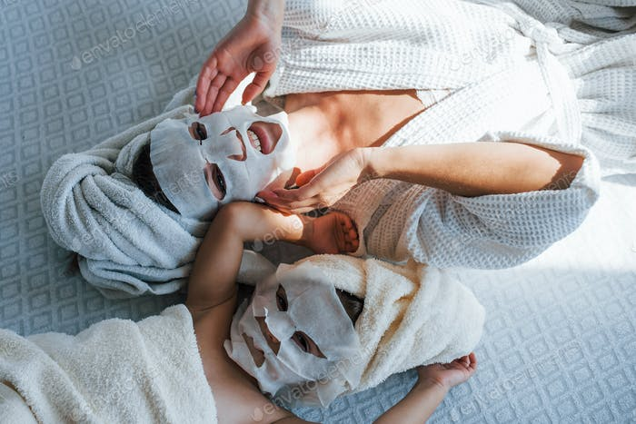 Mother and daughter have spa day with beauty masks on faces. Lying down on bed with towels on heads