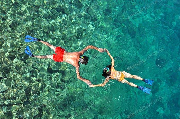 Junges Paar schnorcheln im klaren tropischen Wasser über Korallenriff. Oben-Ansicht