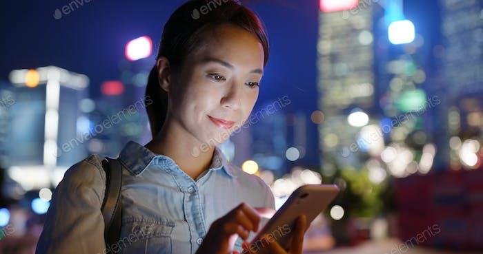 Frau Nutzung des Mobiltelefons online in der Nacht