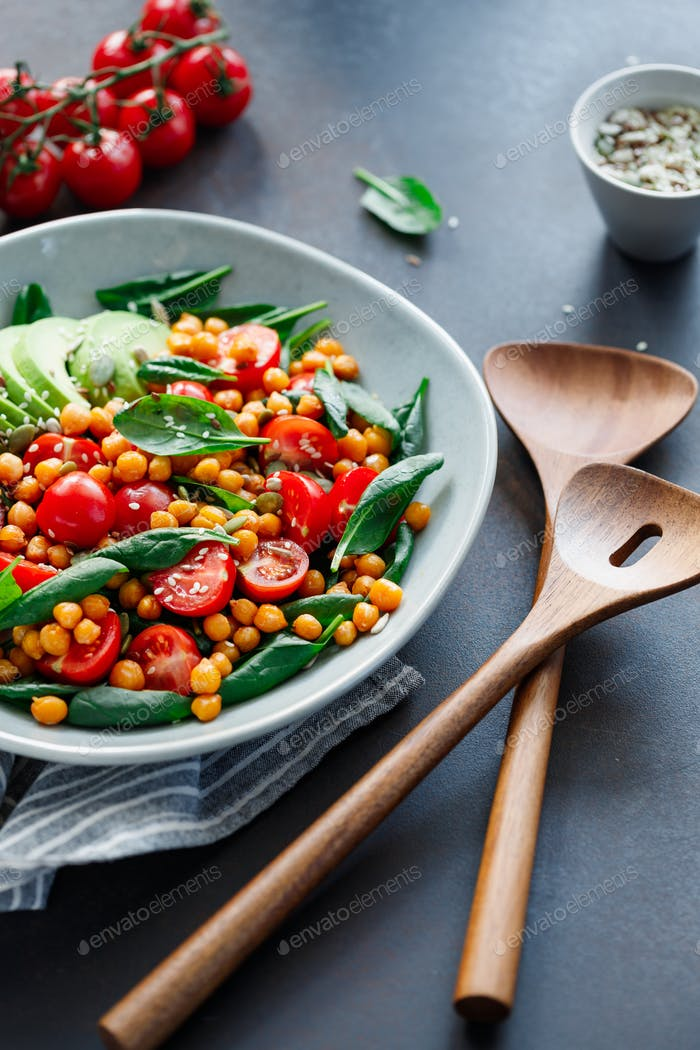 Fresh healthy salad with chickpea, avocado, cherry tomatoes and spinach.